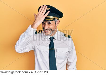Handsome middle age man with grey hair wearing airplane pilot uniform surprised with hand on head for mistake, remember error. forgot, bad memory concept.