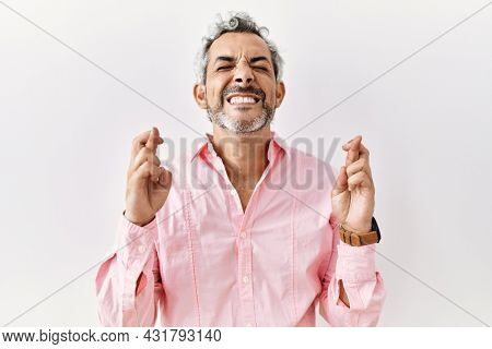 Middle age hispanic man standing over isolated background gesturing finger crossed smiling with hope and eyes closed. luck and superstitious concept.