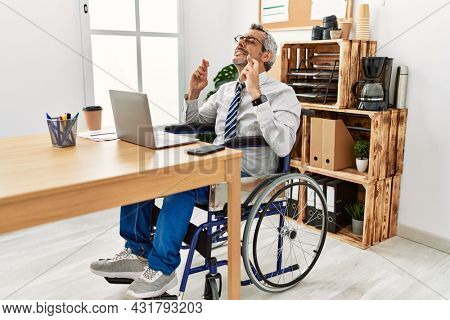 Middle age hispanic man working at the office sitting on wheelchair gesturing finger crossed smiling with hope and eyes closed. luck and superstitious concept.
