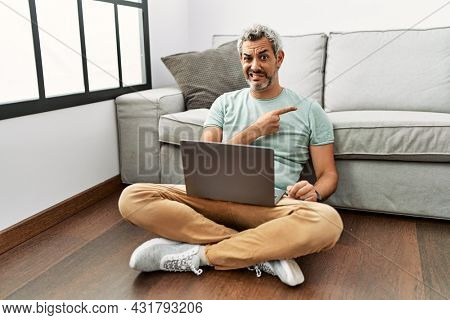 Middle age hispanic man using laptop sitting on the floor at the living room pointing aside worried and nervous with forefinger, concerned and surprised expression