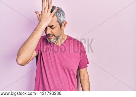 Handsome middle age man with grey hair wearing casual pink t shirt surprised with hand on head for mistake, remember error. forgot, bad memory concept.