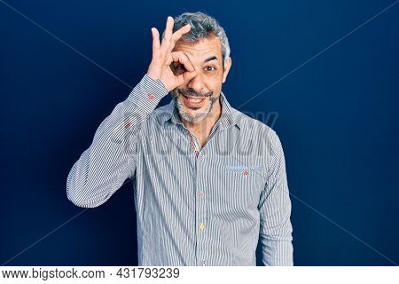 Handsome middle age man with grey hair wearing business shirt doing ok gesture with hand smiling, eye looking through fingers with happy face.
