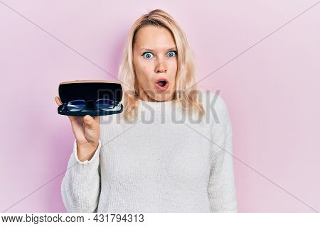 Beautiful caucasian blonde woman holding glasses in eyewear case scared and amazed with open mouth for surprise, disbelief face