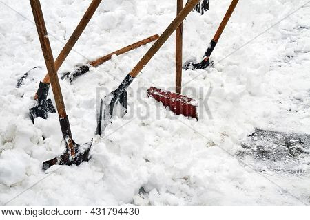 Some Snow Shovels For Snow Removal In Deep Fresh Snow. Snow Removal Concept. Weather Collapse