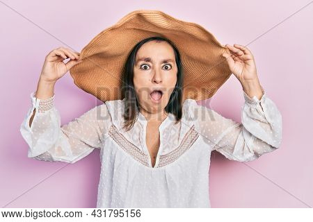 Middle age hispanic woman wearing summer hat afraid and shocked with surprise and amazed expression, fear and excited face.