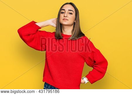 Beautiful brunette woman wearing casual winter sweater suffering of neck ache injury, touching neck with hand, muscular pain