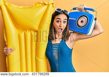 Young brunette girl wearing bikini holding boombox and float afraid and shocked with surprise and amazed expression, fear and excited face.
