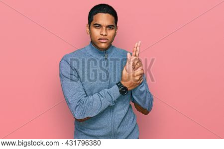 Young handsome hispanic man wearing casual sweatshirt holding symbolic gun with hand gesture, playing killing shooting weapons, angry face