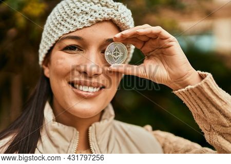 Young latin woman smiling happy holding crypto ethereum coin over eye at the city.