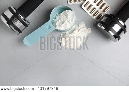 Measuring Scoop Of Amino Acids Powder, Pills And Dumbbells On Light Grey Table, Flat Lay. Space For