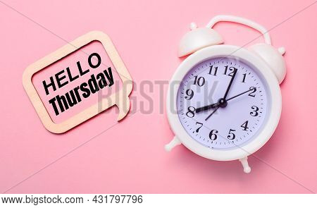 On A Delicate Pink Background, A White Alarm Clock And A Wooden Frame With The Text Hello Thursday