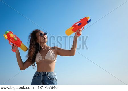 African American Woman With Water Guns Having Fun Against Blue Sky