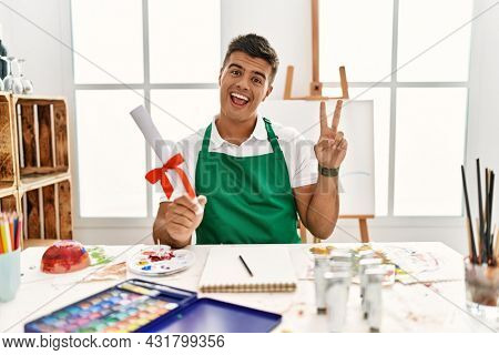 Young hispanic man at art studio holding degree smiling with happy face winking at the camera doing victory sign with fingers. number two.