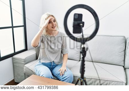 Young caucasian woman recording vlog tutorial with smartphone at home very happy and smiling looking far away with hand over head. searching concept.