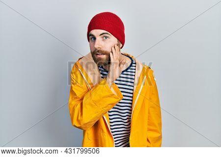 Caucasian man with beard wearing yellow raincoat hand on mouth telling secret rumor, whispering malicious talk conversation