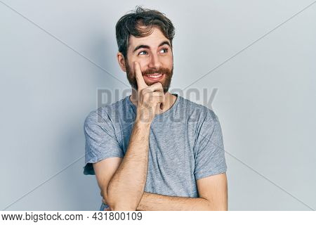 Caucasian man with beard wearing casual grey t shirt with hand on chin thinking about question, pensive expression. smiling with thoughtful face. doubt concept.