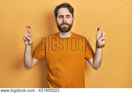 Caucasian man with beard wearing casual yellow t shirt gesturing finger crossed smiling with hope and eyes closed. luck and superstitious concept.