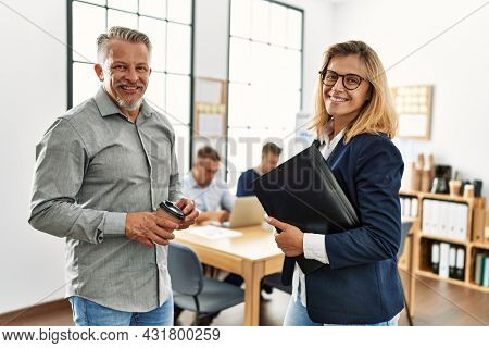 Two middle age business workers speaking while partners working at the office.