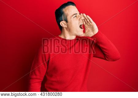 Handsome young man wearing casual winter sweater shouting and screaming loud to side with hand on mouth. communication concept.