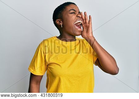 Young african american woman wearing casual yellow t shirt shouting and screaming loud to side with hand on mouth. communication concept.