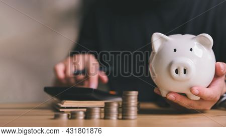 Piggy Bank And Stacking Coins With Man Calculate Income And Expenses, Managing Monthly Household Bud