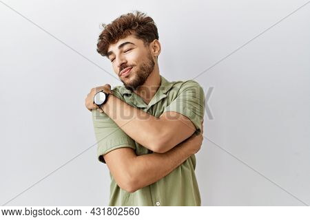 Young arab doctor man standing over isolated background hugging oneself happy and positive, smiling confident. self love and self care