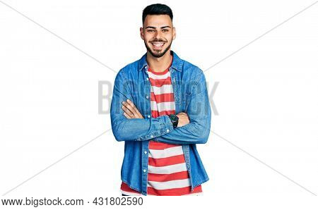 Young hispanic man with beard with arms crossed gesture smiling with a happy and cool smile on face. showing teeth.