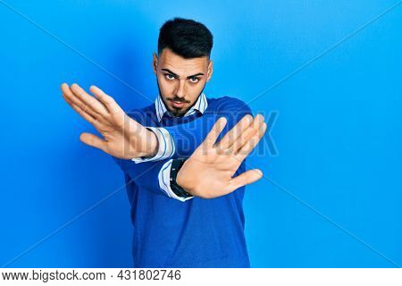 Young hispanic man with beard wearing casual blue sweater rejection expression crossing arms and palms doing negative sign, angry face