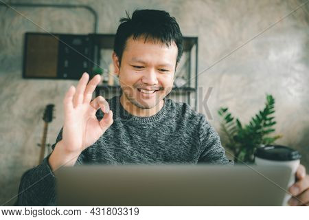 Smiling Young Asian Man Hand Mark Ok Sit At Desk Work On Laptop Making Meeting. Happy Millennial Mal