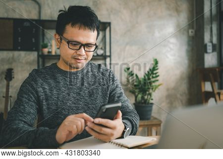 Workplace At Home. A Man Works On A Laptop At Home, Sits On A Disk In The Living Room During The Day