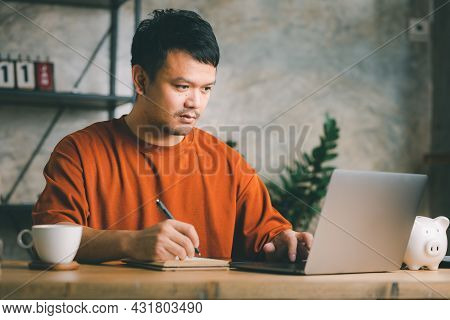 Portrait Of A Smiling Young Asian Man Working On Laptop Computer While Sitting At The Desk With Pape