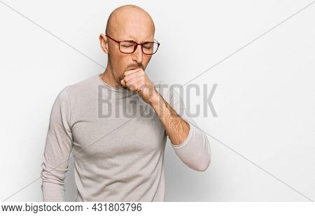 Bald man with beard wearing casual clothes and glasses feeling unwell and coughing as symptom for cold or bronchitis. health care concept.