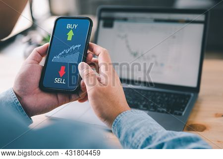 Hand Of Trader Holding Smartphone Looking At Stock Exchange Trading Data Information Displayed With