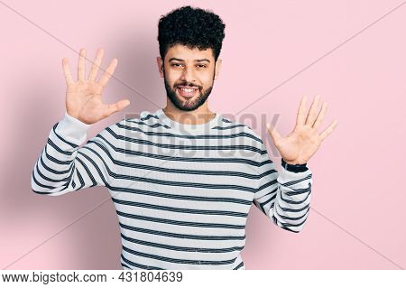 Young arab man with beard wearing casual striped sweater showing and pointing up with fingers number ten while smiling confident and happy.