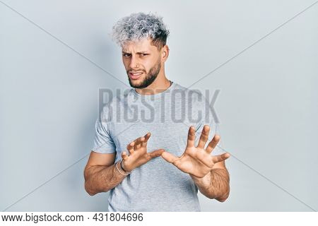 Young hispanic man with modern dyed hair wearing casual grey t shirt disgusted expression, displeased and fearful doing disgust face because aversion reaction. with hands raised