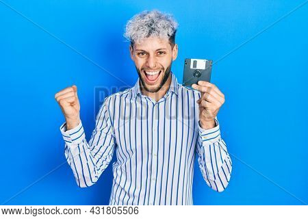 Young hispanic man with modern dyed hair holding floppy disk screaming proud, celebrating victory and success very excited with raised arms