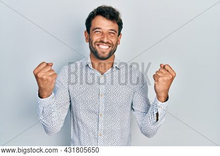 Handsome man with beard wearing casual elegant shirt screaming proud, celebrating victory and success very excited with raised arms