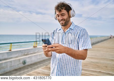 Young hispanic man smiling happy listening to music at the promenade.