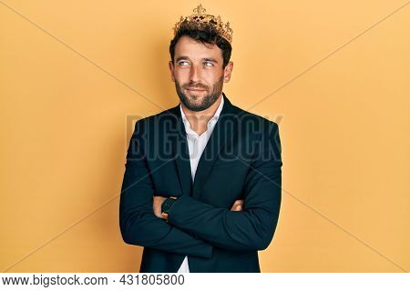 Handsome man with beard wearing business suit with arms crossed gesture and king crown smiling looking to the side and staring away thinking.