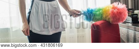 Partial View Of Young Chambermaid In Apron Cleaning Red Armchair With Dust Brush In Hotel Room, Bann