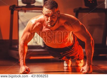 Slim Man Doing Some Push Ups A The Gym. Muscular Man Doing Push-ups On One Hand Against Gym Backgrou