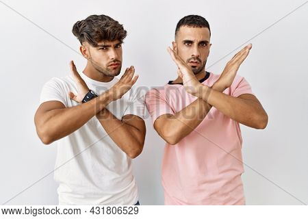 Young gay couple standing over isolated background rejection expression crossing arms doing negative sign, angry face