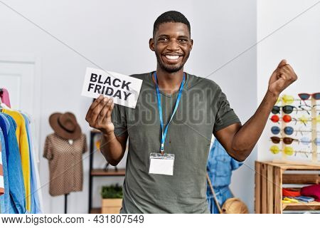 Young african american man holding black friday banner at retail shop screaming proud, celebrating victory and success very excited with raised arm