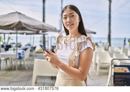 Young chinese girl smiling happy using smartphone at the promenade.