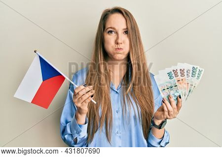 Young blonde woman holding czech republic flag and koruna banknotes puffing cheeks with funny face. mouth inflated with air, catching air.