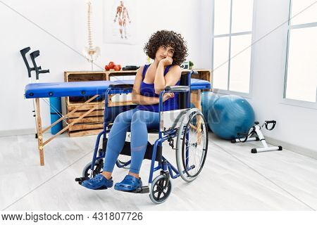 Young middle eastern woman sitting on wheelchair at physiotherapy clinic thinking looking tired and bored with depression problems with crossed arms.