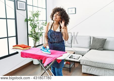 Young middle eastern woman ironing clothes at home smiling with hand over ear listening an hearing to rumor or gossip. deafness concept.