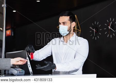 Administrator In Latex Gloves And Medical Mask Giving Room Key To Guest