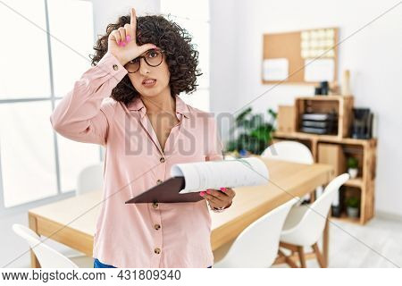 Young middle eastern woman wearing business style at office making fun of people with fingers on forehead doing loser gesture mocking and insulting.