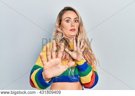 Beautiful young blonde woman wearing colored sweater moving away hands palms showing refusal and denial with afraid and disgusting expression. stop and forbidden.